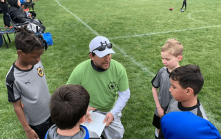 A Wolves Soccer Coach Talks To A Group Of Young Players
